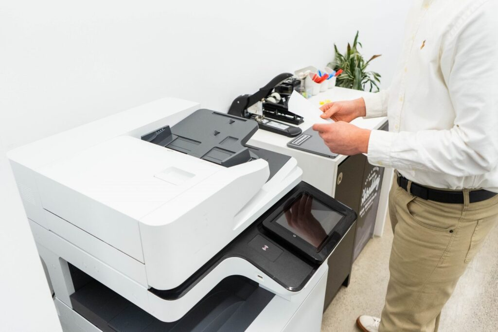 A male employee using white shirt and khaki pants, in front of a printer, picking up his print job