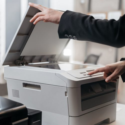 Business woman is using the printer to scanning and printing document