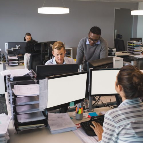 Business colleagues working on computers at desk